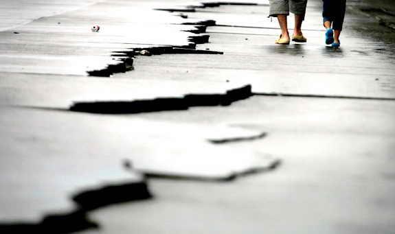 Отец и сын идут возле трещины, которая образовалась от землетрясения в Японии