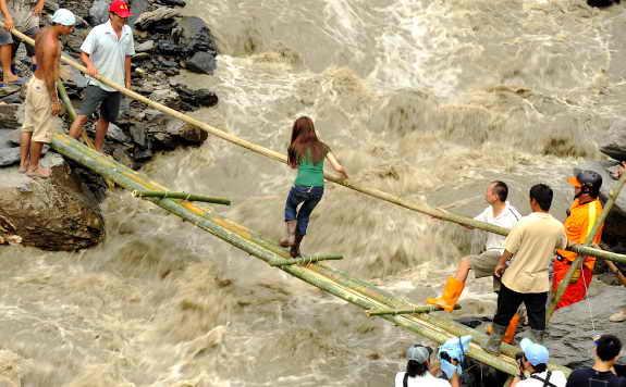 Девушка старается перейти бушующий поток воды через импровизированный мостик во время наводнения в деревне Хсинфа, на юге Тайваня