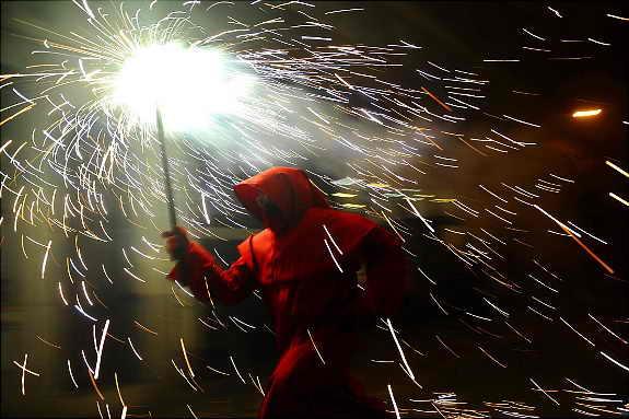"""Участник испанского праздника """"Бега с огнем"""" (""""Correfoc"""") бежит с факелом по Барселоне"""