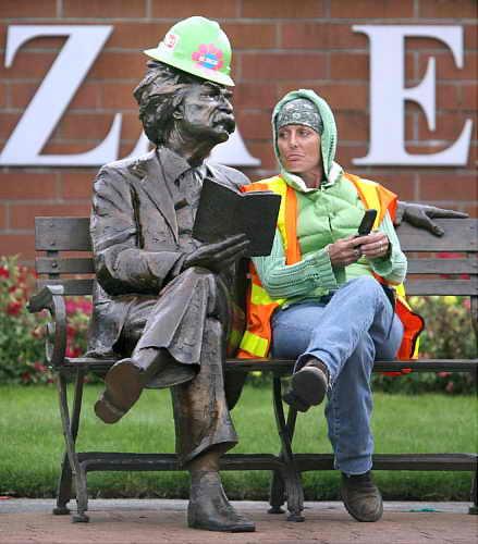 Женщина-укладчица плитки на Бульваре Капитол, Вашингтон, отдыхает возле статуи Марк Твена