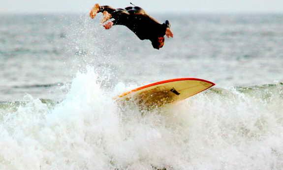 Серфер прыгает по волнам, которые образовались от Урагана Билл в штате Нью Йорк