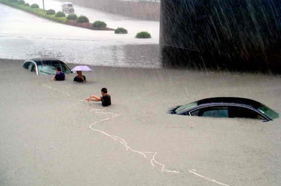 Две машины ушли под воду во время наводнения в городе Венцу, Китай