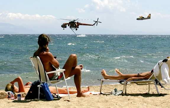 Туристы загорают в то время, как вертолет набирает воду для тушения пожаров в Греции
