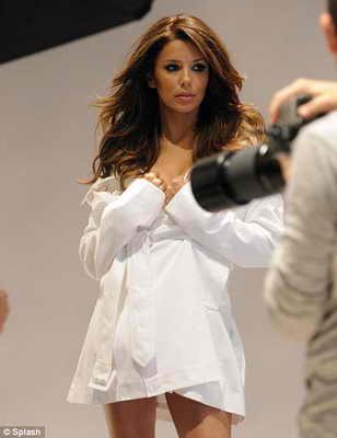 Сексуальная домохозяйка позирует в простой белой рубашке