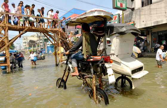 В столице Филиппин Маниле до сих пор не прекращаются обильные дожди после того, как по острову прошел тропический ураган Кетсана. На фото местный житель пытается проехать на мотоцикле по затопленной улице