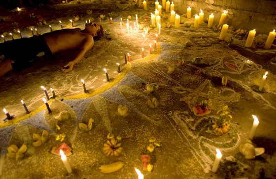 Последователь веры Maria Lionza лежит в кругу, очерченном свечами во время ежегодного собрания последователей веры Последователь веры Maria Lionza на горе Сорте в Венесуэле. Maria Lionza - вера объединившая в себе элементы веры африканских туземцев и католических обрядов, похожа на веру Сантерию