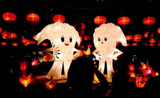 """В Гонконге во время Фестиваля """"Середина осени"""" люди смотрят с восхищением на инсталляцию фонарей, в форме символов Восточно-Азиатских игр 2009"""