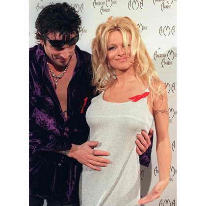 Томми Ли гладит живот беременной жены, Памелы Андерсон, во время 23-й Ежегодной Церемонии American Music Awards в 1996. Они поженились в 1995 году, спустя 96 часов после встречи