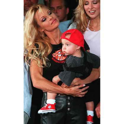 """Памела Ли Андерсон держит своего сына Брэндона, в то время как участники группы """"Motley Crue"""" оставляли отпечатки рук на почетной цементной пластине в Голливуде в мае 2007"""