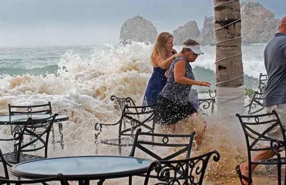 Люди убегают от огромной волны, которая накрыла берег пляжа Медано в Мексике во время урагана Рик, обрушившегося на популярное место отдыха Баджа Калифорния.