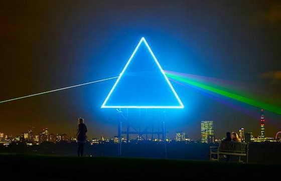 """Прохожие любуются лазерным произведением искусства команды Sky Arts как дань памяти выхода альбома """"Dark Side Of The Moon"""" группы Pink Floyd в Лондоне."""
