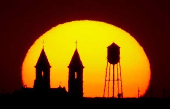 Шпили-близнецы церкви St Fidelis и муниципальная водонапорная вышка на фоне очень красивого заката солнца в городе Виктория в Канзасе.
