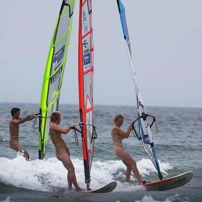 Трое обнаженных серфингистов участвуют в соревновании Tiree Wave в Шотландии