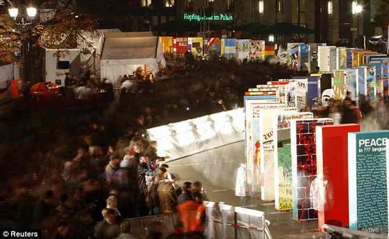 Толпы людей проходят возле домино, символизирующих Берлинскую стену