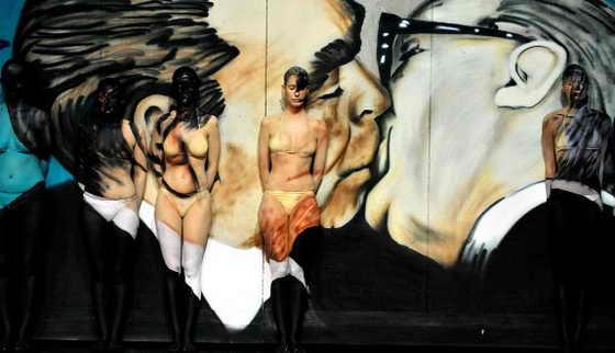 Боди арт модели на празднике в честь годовщины падения Берлинской стены на фоне знаменитой картины поцелуя между тогдашним советским лидером Леонидом Брежневым и Восточно-немецкого лидера Эриха Хонеккера