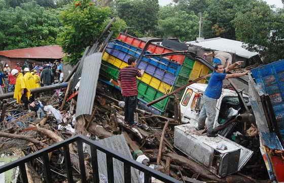 Люди ходят среди того, что осталось от грузовиков на улице, разрушенной в результате проливных дождей в Верапасе