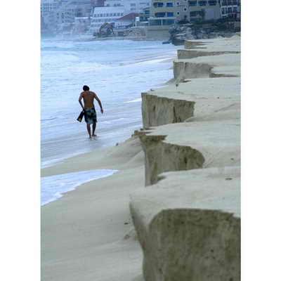 Мужчина прогуливается по пляжу Чак Мул в Канкуне, в штате Кинтана-Роо, Мексика. Силу урагана Ида специалисты отнесли во 2-ю категорию, немного успокоился на подходе к Мексиканскому заливу