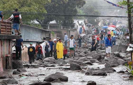 Местные люди смотрят на развалины домов возле реки Акахуапа в Сан-Висенте. Оползни и вышедшие из берегов реки оказались слишком большим испытанием для домов, построенных на дешевом, ненадежном материале... Все улицы завалены валунами