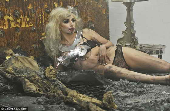 В постели с Леди Гага: Певица позирует в конусобразном бюстгалтере в стиле Мадонны на обгоревшем матрасе вместе со скелетом