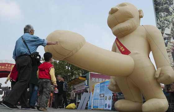"""Люди смотрят на эрогированную надувную фигуру в китайском городе Ханьчжоу, поставленную в честь праздника """"Мужской день здоровья"""""""