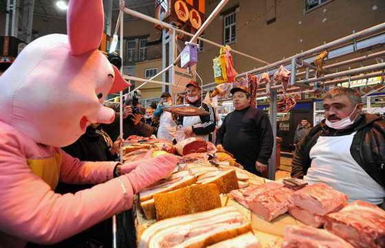 """Мужчина, одетый в костюм свиньи, символизирующей свиной грипп """"нападает"""" на мясников во время комического представления студентов на Бессарабском рынке в Киеве"""