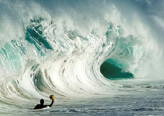 Кларк Литтл делает фотографии волны, находясь в воде, недалеко от гавайского пляжа Laniakea