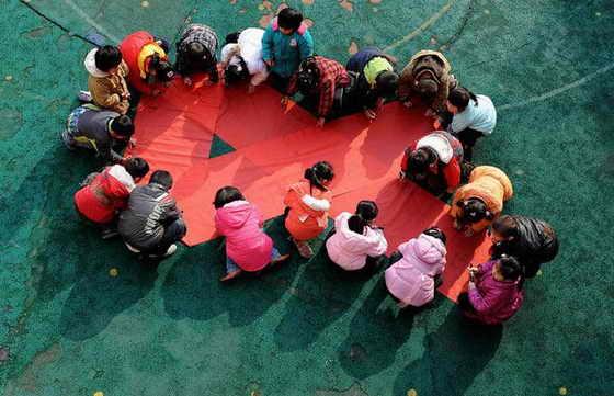 Дети пишут свои имена на красной ленточке во время акции по поднятию осведомленностьи о ВИЧ / СПИДе в детском саду в Хэфэй, провинция Аньхой, Китай
