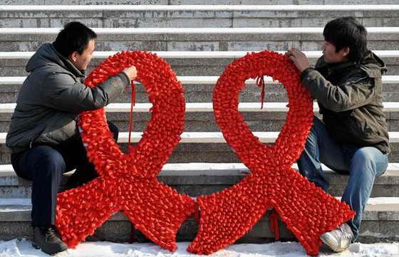 Студенты делают большие красные ленты на улице во время акции о поднятии осведомленности о ВИЧ / СПИДе во Всемирный день борьбы со СПИДом в Шеньян, провинция Ляонин, Китай
