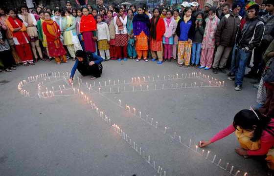 Люди молятся, стоя со свечами, в одном из центров для ВИЧ-инфицированных детей и женщин, ставшими жертвами торговли людьми в Катманду, Непал