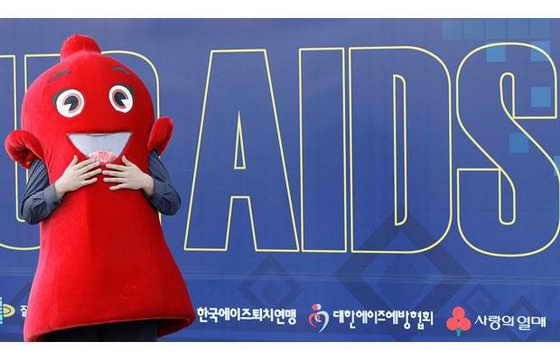 Работника, одетый в красную форму-презерватив приобщает к использованию презервативов во время кампаний, поднимающей сознательность и осведомленность о СПИДе в Сеуле, Южная Корея