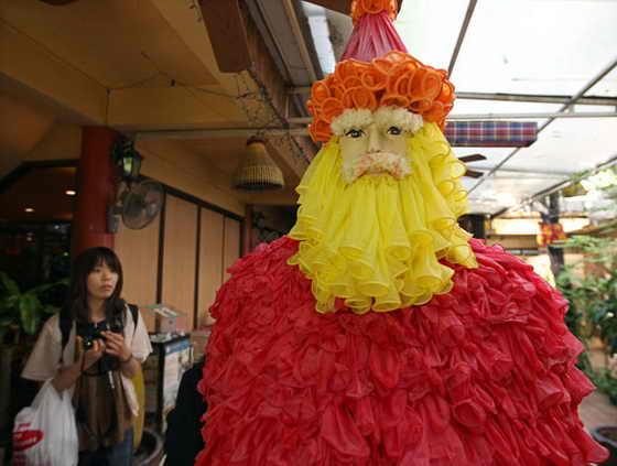 Японский турист смотрит на фигуру Санты Клауса из презервативов в Бангкоке
