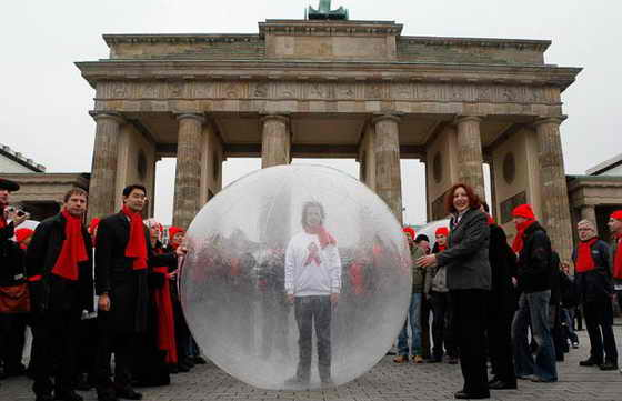 Учстник кампании по борьбе со СПИДом стоит в пластиковом пузыре в окружении работников здравоохранения перед Бранденбургскими воротами в Берлине. Пузырь символизировает стигматизацию людей, живущих с ВИЧ и СПИДом