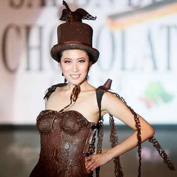 Модель идет в шоколадном платье и цилиндре на модном шоколадном шоу Salon du Chocolat в Шанхае, Китай