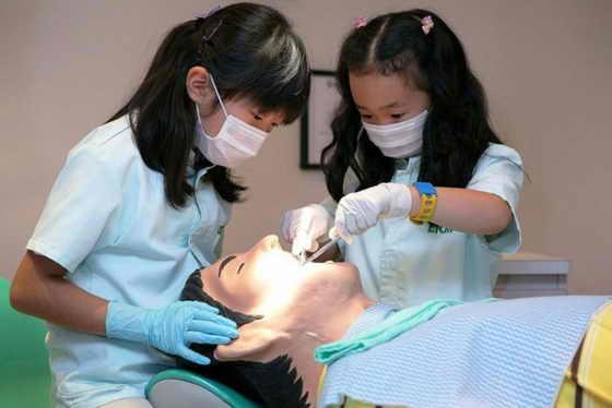 Дети осматривают манекен во время игры в дантистов