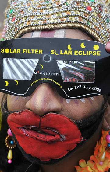 Индийский художник Б. Nookaджи, одетый как индусский бог-обезьяна Ханумана, использует специальные солнечные очки, чтобы посмотреть на солнечное затмение в Хайдарабаде