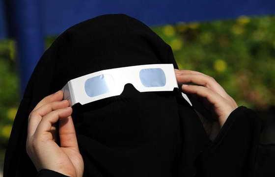 Женщина из Саудовской Аравии использует специальные очки с тонированными стеклами для наблюдения за частичным солнечным затмением в портовом городе Джидда