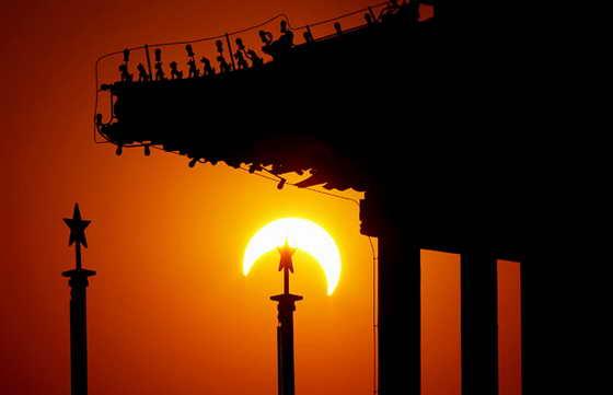 Луна начинает находить на Солнце - вид с Земли в Шеньян, провинция Ляонин, Китай