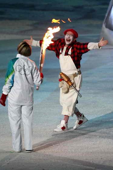 Бывшая конькобежка Катриона Мей Доан стоит с олимпийским факелом с мимом Ивом Дажене, которые завершает свое выступление во время церемонии закрытия в Ванкувере зимних Олимпийских играх 2010