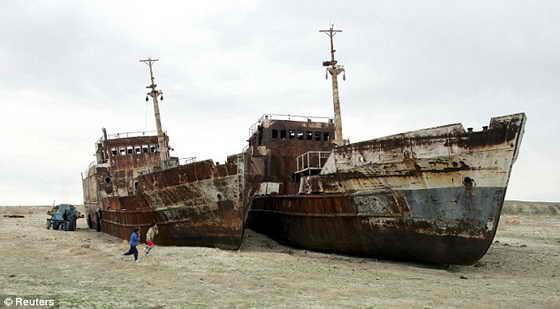Дети играются возле брошенных кораблей в высохшем Аральском море